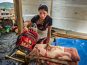 02 AUGUST 2015 - BHAKTAPUR, NEPAL:  A woman sets up her family's living space in a small Internal Displaced Person (IDP) camp at Durbar Square in Bhaktapur for people left homeless by the Nepal earthquake. The Nepal Earthquake on April 25, 2015, (also known as the Gorkha earthquake) killed more than 9,000 people and injured more than 23,000. It had a magnitude of 7.8. The epicenter was east of the district of Lamjung, and its hypocenter was at a depth of approximately 15 km (9.3 mi). It was the worst natural disaster to strike Nepal since the 1934 Nepal–Bihar earthquake. The earthquake triggered an avalanche on Mount Everest, killing at least 19. The earthquake also set off an avalanche in the Langtang valley, where 250 people were reported missing. Hundreds of thousands of people were made homeless with entire villages flattened across many districts of the country. Centuries-old buildings were destroyed at UNESCO World Heritage sites in the Kathmandu Valley, including some at the Kathmandu Durbar Square, the Patan Durbar Squar, the Bhaktapur Durbar Square, the Changu Narayan Temple and the Swayambhunath Stupa. Geophysicists and other experts had warned for decades that Nepal was vulnerable to a deadly earthquake, particularly because of its geology, urbanization, and architecture.      PHOTO BY JACK KURTZ