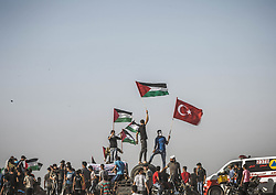 July 6, 2018 - Gaza City, Gaza - Young Palestinian demonstrators display the Palestinian flag and the turkish flag during the confrontation with the Israeli forces east of Gaza City along the border between the Gaza strip and Israel..Palestinian of Gaza demonstration and confronted with the Israeli forces near the border with Israel as part of the ''Great March of Return'' movement, the Israeli forces retaliated with tear gas. (Credit Image: © Nidal Alwaheidi/SOPA Images via ZUMA Wire)