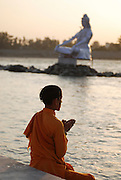 India, Pilgrims bathe in the Ganges River Statue of Buddha in the background