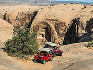Two Hummers parked next to a canyon called the Abyss on a  4x4 Hummer tour on the Hell's Revenge Trail in the Sandflats Recreation Area near Moab, Utah.