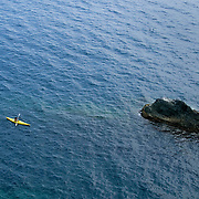 A woman in a yellow ocean kayak paddles near a large rock in the Mediterranean Sea of the Cinque Terre region of Italy. The Cinque Terre is a string of centuries-old seaside villages on the rugged Italian Riviera coastline.