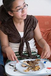 Portrait of a teenage girl watching television and eating her dinner,