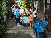 27 AUGUST 2016 - BANGKOK, THAILAND: A juice vendor sells fresh bottled juices to residents of the Pom Mahakan slum. The Pom Mahakan community is known for fireworks, fighting cocks and bird cages. Mahakan Fort was built in 1783 during the reign of Siamese King Rama I. It was one of 14 fortresses designed to protect Bangkok from foreign invaders. Only two of the forts are still standing, the others have been torn down. A community developed in the fort when people started building houses and moving into it during the reign of King Rama V (1868-1910). The land was expropriated by Bangkok city government in 1992, but the people living in the fort refused to move. In 2004 courts ruled against the residents and said the city could evict them. The city vowed to start the evictions on Sept 3, 2016, but this week Thai Prime Minister Gen. Prayuth Chan-O-Cha, sided with the residents of the fort and said they should be allowed to stay. Residents are hopeful that the city will accede to the wishes of the Prime Minister and let them stay.       PHOTO BY JACK KURTZ