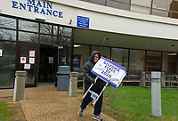 Julie Andrews leaves Gilford High School with a stack of signs to deliver to the homes of the 2020 graduating seniors on Monday morning.  (Karen Bobotas/for the Laconia Daily Sun)