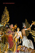 A traditionally costumed Thai man and woman are dancing on a passing float during the annual Loi Krathong Festival parade in Chiang Mai, Thailand.