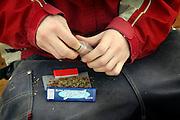Nederland, Eindhoven, 24-3-2005..Jongen, jongere, maakt een joint, stickie, stikkie, blow met wiet, nederwiet op straat. Drugs, soft, marihuana, drugsbeeid, gedoogbeleid, gedogen, kleine gebruiker, eigen gebruik, handel...Foto: Flip Franssen/Hollandse Hoogte