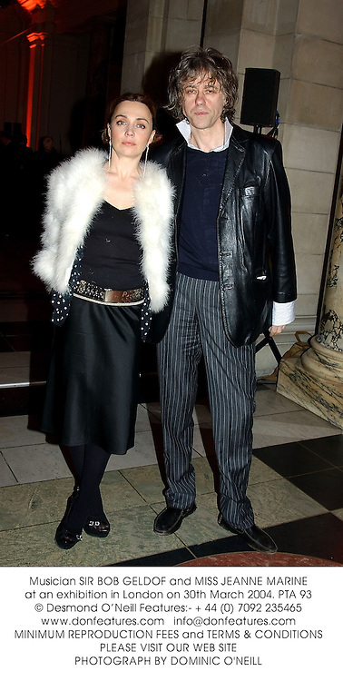 Musician SIR BOB GELDOF and MISS JEANNE MARINE at an exhibition in London on 30th March 2004.PTA 93