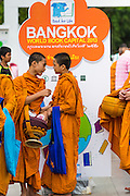 "23 APRIL 2013 - BANGKOK, THAILAND:  Buddhist monks and novices walk past a sign announcing Bangkok is the 2013 UNESCO World Book Capital. UNESCO awarded Bangkok the title. Bangkok is the 13th city to assume the title of ""World Book Capital"", taking over from Yerevan, Armenia. Bangkok Governor Suhumbhand Paribatra announced plans that the Bangkok Metropolitan Administration (BMA) intends to encourage reading among Thais. The BMA runs 37 public libraries in the city and has modernised 14 of them. It plans to build 10 more public libraries every year. Port Harcourt, Nigeria will be the next World Book Capital in 2014. <br /> PHOTO BY JACK KURTZ"