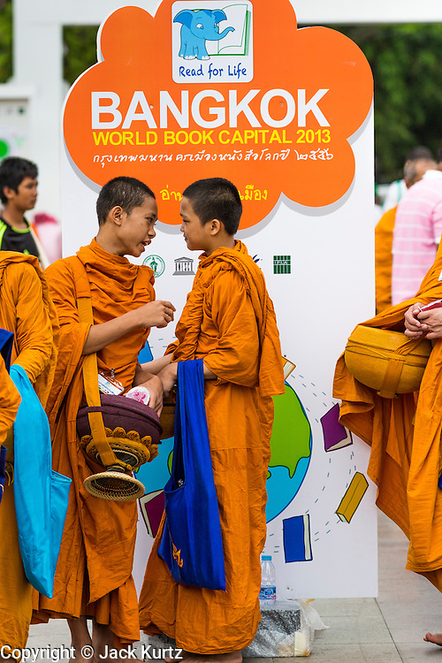 """23 APRIL 2013 - BANGKOK, THAILAND:  Buddhist monks and novices walk past a sign announcing Bangkok is the 2013 UNESCO World Book Capital. UNESCO awarded Bangkok the title. Bangkok is the 13th city to assume the title of """"World Book Capital"""", taking over from Yerevan, Armenia. Bangkok Governor Suhumbhand Paribatra announced plans that the Bangkok Metropolitan Administration (BMA) intends to encourage reading among Thais. The BMA runs 37 public libraries in the city and has modernised 14 of them. It plans to build 10 more public libraries every year. Port Harcourt, Nigeria will be the next World Book Capital in 2014. <br /> PHOTO BY JACK KURTZ"""