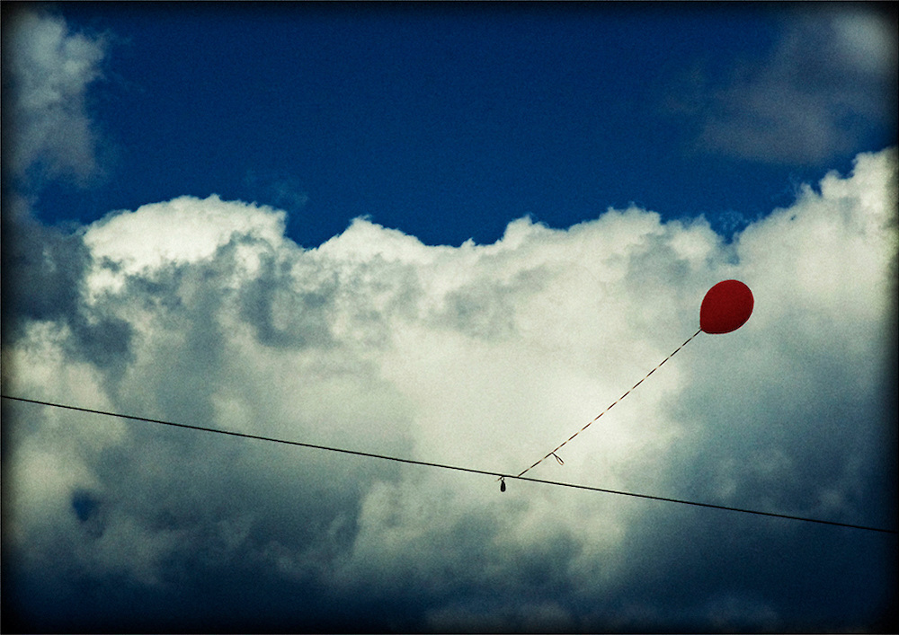 An errant red balloon stuck on a wire against clouds and blue sky at the annual Grange Fair.