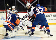 New York Islanders goalie Kevin Poulin (60) and defenseman Brian Strait (37) defend against New Jersey Devils right wing Sergey Kalinin (51) and center Reid Boucher (32) during an NHL preseason hockey game Wednesday, Sept. 23, 2015 at Barclays Center in New York. (AP Photo/Kathy Kmonicek)