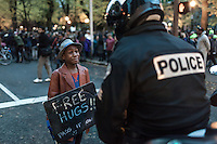 Devonte Hart and Portland, Oregon police officer Bret Barnum have their special moment.  Protest in front of the Justice Center to protest the Mike Brown, Ferguson verdict.  ©jan sonnenmair 2014.  All rights reserved. Devonte Hart, Portland Oregon