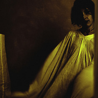 A young woman wearing a long yellow garment in a dark room