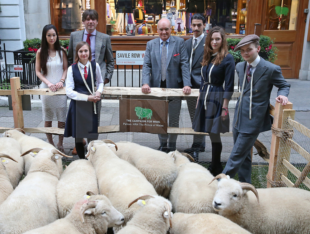 © Licensed to London News Pictures. 05/10/2015. London, UK.  ALEX JAMES (3L) joins NICHOLAS COLERIDGE (4L) and apprentices for the launch of Wool Week 2015. Savile Row is transformed with sheep and grass.  Photo credit: Peter Macdiarmid/LNP