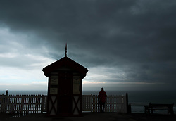 © Licensed to London News Pictures. 07/04/2014<br /> <br /> Saltburn, United Kingdom<br /> <br /> A woman stands next to the cliff lift as dark storm clouds form over Saltburn by the Sea in Cleveland.<br /> <br /> Photo credit : Ian Forsyth/LNP