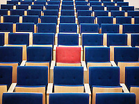 One Red Seat in large group of blue seats in auditorium
