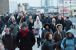© Licensed to London News Pictures. 03/01/2018. London, UK. Commuters cross London Bridge during stormy and windy weather, as Storm Eleanor hits London this morning. Photo credit: Vickie Flores/LNP