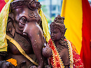 "07 SEPTEMBER 2014 - BANGKOK, THAILAND: Statue of Ganesh, the ""Overcomer of Obstacles"" with his mother, Shiva at the Ganesh Festival in Bangkok. Ganesh Chaturthi, also known as Vinayaka Chaturthi, is a Hindu festival dedicated to Lord Ganesh. It is a 10-day festival marking the birthday of Ganesh, who is widely worshiped for his auspicious beginnings. Ganesh is the patron of arts and sciences, the deity of intellect and wisdom -- identified by his elephant head. The holiday is celebrated for 10 days, in 2014, most Hindu temples will submerge their Ganesh shrines and deities on September 7.     PHOTO BY JACK KURTZ"