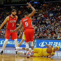 Feb 14, 2018; New Orleans, LA, USA; Los Angeles Lakers guard Isaiah Thomas (7) is tripped up driving between New Orleans Pelicans guard Rajon Rondo (9) and forward Nikola Mirotic (3) during the first quarter at the Smoothie King Center. Mandatory Credit: Derick E. Hingle-USA TODAY Sports