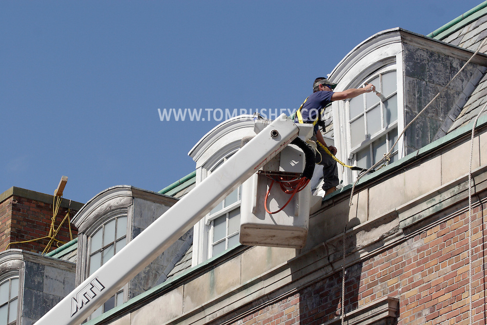 Middletown - A worker on a lift paints the windors on the roof of a building in downtown Middletown on May 23, 2008.