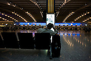 Stranded passenger awaits next flight in the morning from near-empty departures concourse at Heathrow's terminal 5.