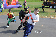 From left, Antonio Rivera, 5 as Robin and Rob Smith, 9 as Batman chase after Paul Sommerfeld, 8 as Michael Myers at the annual fall festival Saturday October 24, 2015 in Bristol Township, Pennsylvania. (Photo by William Thomas Cain)