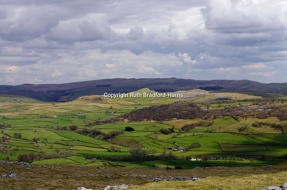 A panoramic view over Crummackdale from Norber, above Austwick, North Yorkshire. The distinctive outline of the inclined Smearsett Scar and the field systems of the valley floor are highlighted by late afternoon sun against the violet-hued dark hills of Malham Moor under a stormy sky.<br /> <br /> Date taken: 30 April 2013.