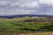 A panoramic view over Crummackdale from Norber, above Austwick, North Yorkshire. The distinctive outline of the inclined Smearsett Scar and the field systems of the valley floor are highlighted by late afternoon sun against the violet-hued dark hills of Malham Moor under a stormy sky.<br />
