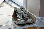 Brown, hi-top sneakers by sliding door leading to the backyard.