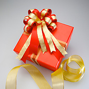 A boxed and wrapped present with an ornate bow to and strand of ribbon symbolize a preparing a gift.