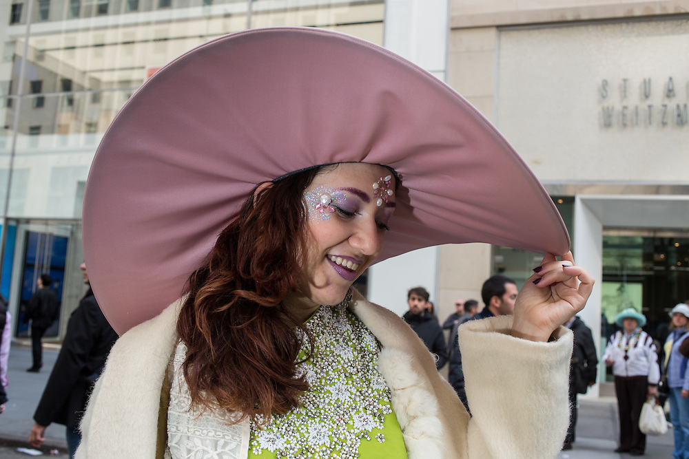 New York, NY, USA-27 March 2016. A woman with glittery face makeup wears a wide-brimmed hat  in the annual Easter Bonnet Parade and Festival.