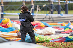 © Licensed to London News Pictures. 04/11/2018. Woking, UK. A police forensics photographer gathers evidence next to a deflated slide in Woking Park after it collapsed injuring eight children. The park was holding a fireworks party when the accident happened. Photo credit: Peter Macdiarmid/LNP