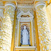 Statue in alcove of the distinctive  and ornate yellow and white exterior of the Iglesia y Convento de Nuestra Senora de la Merced in downtown Antigua, Guatemala.