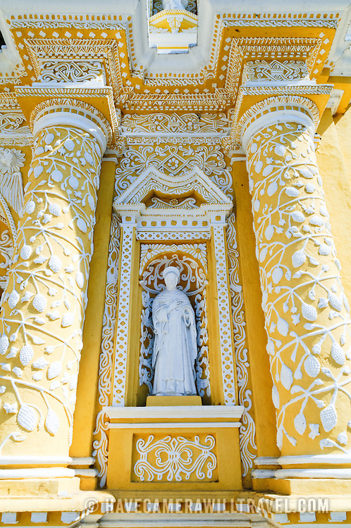 Statue in alcove of the distinctive  and ornate yellow and white exterior of the Iglesia y Convento de Nuestra Senora de la Merced in downtown Antigua, Guatemala.