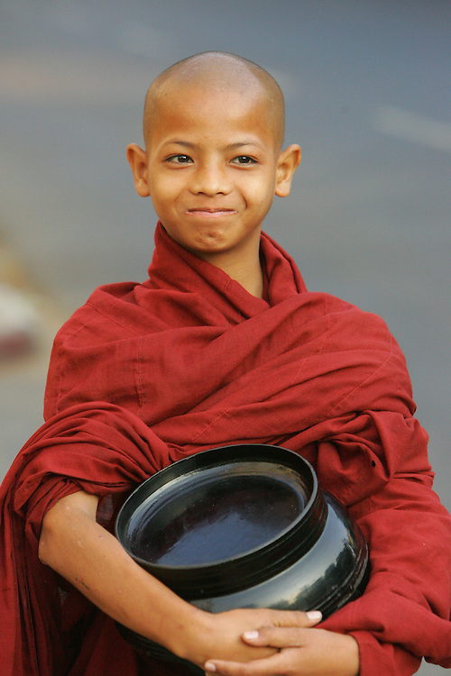 A novice Burmese Buddhist monks looks on during his early morning walk in downtown Rangoon.