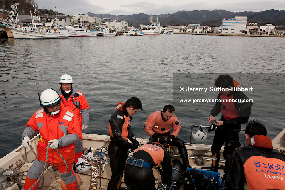 Divers and ground crews of the Japanese coast guard search underwater in the harbour for the bodies of victims of the March 11th 2011 tsunami, in Kesennuma, Japan, on Tuesday 14th February 2012.