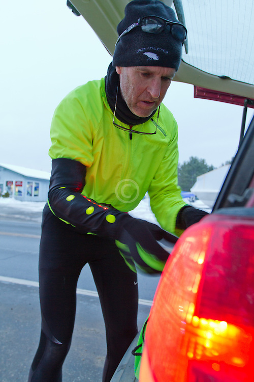 Gary Allen runs from Maine to Washington DC, putting on Glimmer Gear as dusk approaches along Bath Road near Brunswick