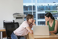 Colleagues using laptop at desk in office