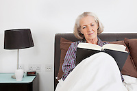 Senior woman reading book in bedroom at home