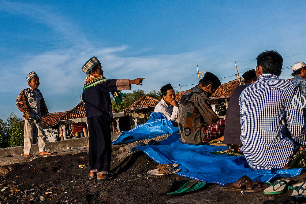 "DEMAK, INDONESIA - OCTOBER 15: Indonesian muslim boy point at his friend during Eid Al-Adha prayer while frequently flood hitting the land in Demak, Central Java, Indonesia, Tuesday, October 15, 2013. World Muslim people celebrate Eid Al Adha or ""The Feast of the Sacrifice"" by slaughtering goats, sheeps, and cattles to honor the Prophet Abraham who tested by God to sacrifice his son Ishmael"