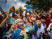 23 JUNE 2016 - MAHACHAI, SAMUT SAKHON, THAILAND:  A man dressed in a Burmese attire dances while supporters of Aung San Suu Kyia wave a Burmese flag during  Suu Kyi's visit to the Burmese community in Samut Sakhon, a province south of Bangkok. Tens of thousands of Burmese migrant workers, most employed in the Thai fishing industry, live in Samut Sakhon. Aung San Suu Kyi, the Foreign Minister and State Counsellor for the government of Myanmar (a role similar to that of Prime Minister or a head of government), is on a state visit to Thailand. Even though she and her party won the 2015 elections by a landslide, she is constitutionally prohibited from becoming the President due to a clause in the constitution as her late husband and children are foreign citizens       PHOTO BY JACK KURTZ