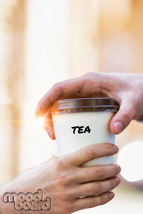 Close up photo of businesswoman giving businessman a cup of tea