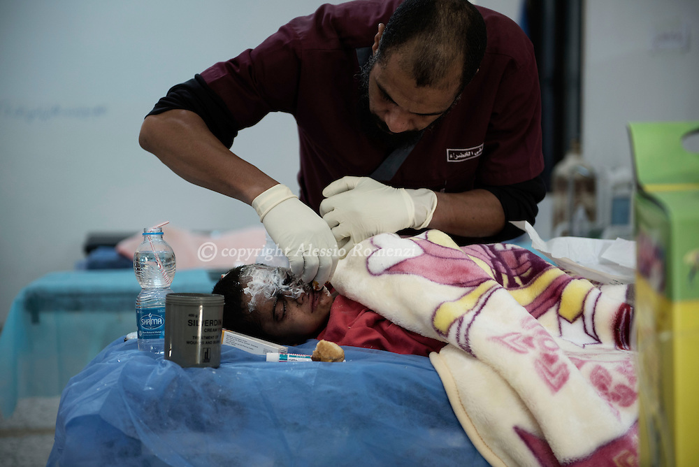 Libya, Sirte: a Libyan doctor cleans excoriations and burns on a child just taken, by fighters of the Libyan forces affiliated to the Tripoli government, out of the fighting area in Sirte. Alessio Romenzi