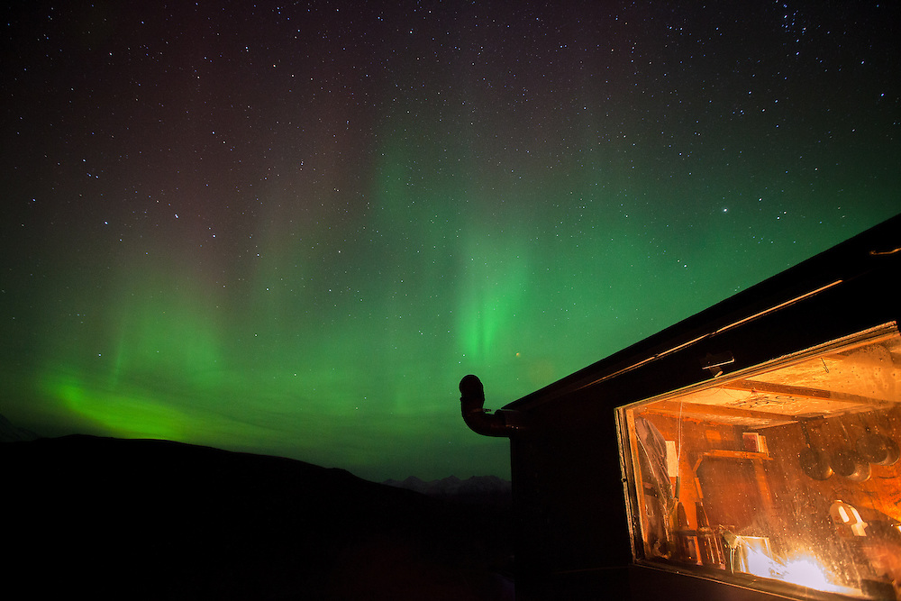 Northern lights (Aurora Borealis) dance over the Mountains while hikers stay warm by the fire in a cozy cabin.