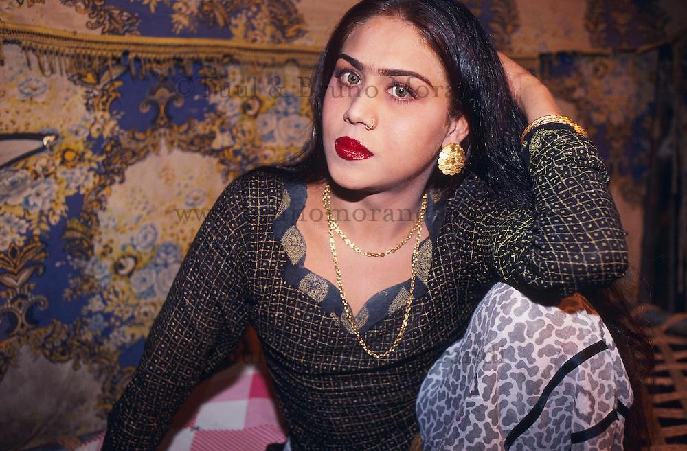 """Pakistan - Hijra, les demi-femmes du Pakistan - Nadra : 22 ans, elle travaille depuis 8-9 ans. Beaucoup d'Hijra ont subit une opération, mais Nadra est une Hijra naturelle. Elle est de Bahawalpur. Sa famille a accepté la situation.<br /> Elle a 4 serviteurs qui lui repassent ses affaires, l'aide à se préparer, à attacher ses chaussures pour danser. // Pakistan. Punjab province. Hijra, the half woman of Pakistan. Nadra, 22 years old. She has been working since 8 or 9 years as Kushra. A lot of Hijra had surgery but Nadra is one of the rare """"natural"""" Hijras. She comes from the region of Bahawalpur and her family accepted her situation. She has 4 servants who help her to prepare herself, to make up, to iron her clothes before going to dance."""
