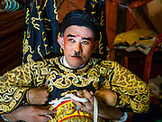 17 FEBRUARY 2016 - BANGKOK, THAILAND: A Chinese opera performer gets into costume backstage before a performance in Bangkok. The small troupe travels from Chinese shrine to Chinese shrine performing for a few nights before going to another shrine. They spend about half the year touring in Thailand and the other half of the year touring in Malaysia. Members of the troupe are paid about 5,000 Thai Baht per month (about $140 US). Chinese opera was once very popular in Thailand, where it is called Ngiew. It is usually performed in the Teochew language. Millions of Chinese emigrated to Thailand (then Siam) in the 18th and 19th centuries and brought their culture with them. Recently the popularity of ngiew has faded as people turn to performances of opera on DVD or movies. There are still as many 30 Chinese opera troupes left in Bangkok and its environs. They are especially busy during Chinese New Year and Chinese holiday when they travel from Chinese temple to Chinese temple performing on stages they put up in streets near the temple, sometimes sleeping on hammocks they sling under their stage. Most of the Chinese operas from Bangkok travel to Malaysia for Ghost Month, leaving just a few to perform in Bangkok.     PHOTO BY JACK KURTZ