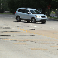 A car cuts through moves across Mall Drive past the potholes on Monday as it enters The Mall at Barnes Crossing in Tupelo.