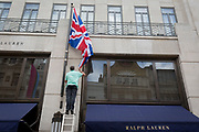 An employee renews the British Union Jack flag outside American clothing retailer Ralph Lauren's Bond Street address, on 5th June 2019, in London, England.