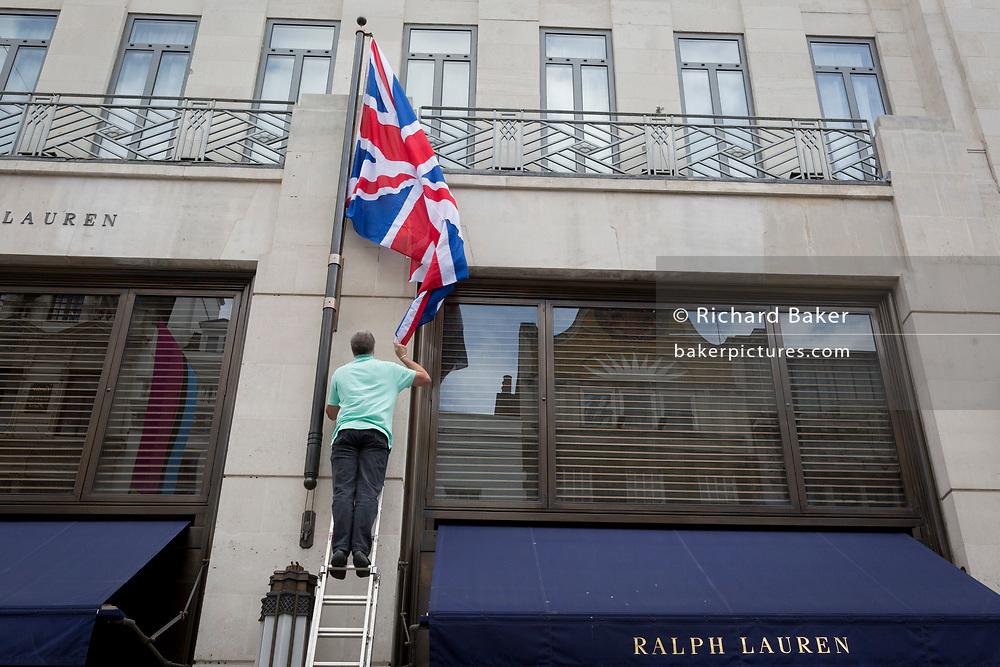 An employee renews the British Union Jack flag outside American clothing retailer Ralph Lauren's Bond Street address, on 5th June 2019, in London, England.