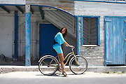 Female European Tourist rides a bicycle on the Caribbean island of Grand Turk